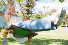 Mature couple at swing in the park Royalty Free Stock Photos