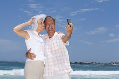 Mature couple taking photograph of themselves on beach with mobile phone, smiling, low angle view Royalty Free Stock Photo