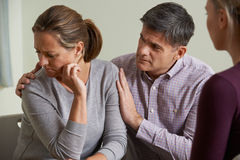 Mature Couple Talking With Counsellor As Man Comforts Woman Royalty Free Stock Photos