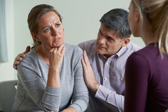 Mature Couple Talking With Counsellor As Man Comforts Woman Stock Images