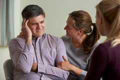 Mature Couple Talking With Counsellor As Woman Comforts Man. Mature Couple Talk With Counsellor As Woman Comforts Man royalty free stock images
