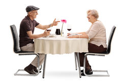 Mature couple talking on a date. Mature couple talking to each other seated at a romantic table on a date isolated on white background stock photos