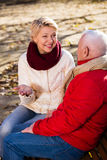 Mature couple talking in park. Mature men and women sitting and talking on bench in park stock photo