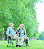 Mature couple talking seated on bench in park Stock Photos