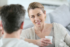 Mature couple talking to eachother at home and drinking coffee stock photos
