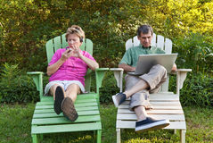 Mature Couple with Their Electronic Devices Royalty Free Stock Photography