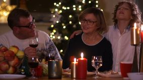 Mature couple with their grandson at the Christmas table at dusk. A woman rejoices, smiles, sings.  stock footage