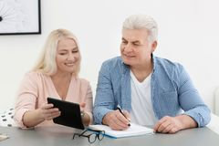 Mature couple thinking over pension payment. At home royalty free stock images