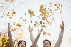 Mature Couple Throwing Leaves into the Air and Having Fun in in Autumn stock photography
