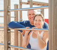 Mature couple together training on pull-up bar Royalty Free Stock Images