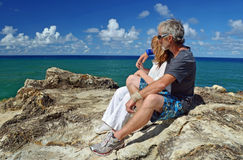 Mature couple top of cliff on tropical island. A loving mature men and women on holiday, embracing each other sitting on top a very high cliff enjoying the Stock Photos