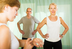 Mature couple with trainer at gym Stock Photos