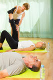 Mature couple with trainer at gym Royalty Free Stock Images