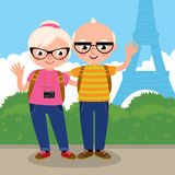 Mature couple travels to Paris. Stock vector illustration of an elderly couple travelers waving a greeting on a background of the Eiffel Tower in Paris stock illustration