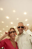 Mature couple trying on sunglasses in shop, price tag attached, smiling, portrait, low angle view Royalty Free Stock Photos