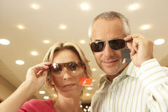 Mature couple trying on sunglasses in shop, price tag attached, smiling, portrait, low angle view Royalty Free Stock Photography