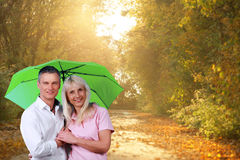Mature couple with umbrella in front of autumn background Royalty Free Stock Photo