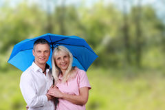 Mature couple with umbrella in front of nature background Royalty Free Stock Photo