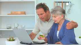 Mature couple using a credit card Royalty Free Stock Image