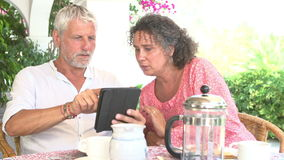Mature Couple Using Digital Tablet At Breakfast Table. Mature couple using digital tablet whilst having breakfast outdoors together.Shot on Sony FS700 at frame stock video