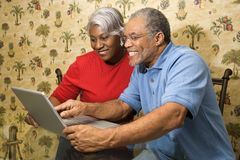 Mature couple using laptop. Portrait of mature African American couple looking at laptop in home Stock Images