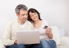 Mature couple using laptop at home Stock Images