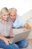 Mature couple using laptop on sofa at home Royalty Free Stock Photo
