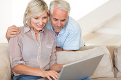Mature couple using laptop on sofa Royalty Free Stock Image