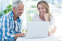 Mature couple using laptop at table Royalty Free Stock Images