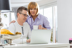Mature couple using laptop together at table in house Stock Image