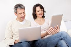 Mature couple using laptops in couch Royalty Free Stock Image