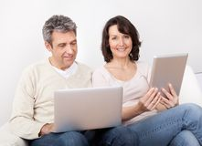 Mature couple using laptops in couch Stock Photos