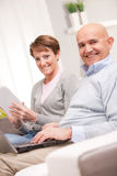 Mature couple using mobile devices. Old women and old men happy together because they love each other in a living room on a sofa Royalty Free Stock Photos