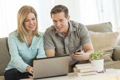 Mature Couple Using Mobile Phone And Laptop On Sofa Stock Photo
