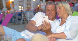 Mature couple using smart phone on the beach. Senior man and woman using mobile phone while relaxing on the beach in the evening. Outdoor cafe in background stock footage