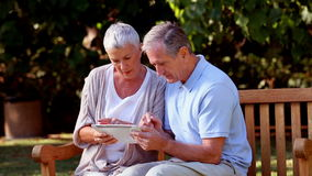 Mature couple using tablet computer on a bench stock video