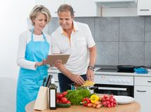 Mature couple using tablet while cooking Stock Photos