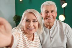 Mature couple using video chat at home stock photo