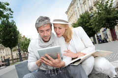 Mature couple visiting city with tablet and map. Couple visiting city with help of map and electronic tablet royalty free stock photo