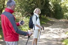 A mature couple walking along a country path, navigating with a smartphone Stock Images
