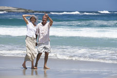 Mature couple walking along sandy beach, man pointing, Atlantic Ocean in background Royalty Free Stock Image