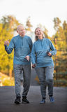 Mature couple walking along street outdoors Stock Photo
