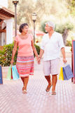 Mature Couple Walking Along Street With Shopping Bags Stock Images