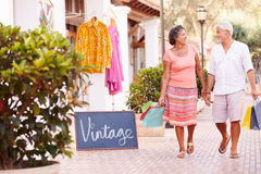 Mature Couple Walking Along Street With Shopping Bags royalty free stock image