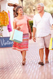 Mature Couple Walking Along Street With Shopping Bags royalty free stock photos