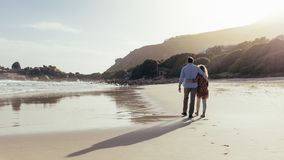 Loving mature couple on a beach walk stock photo