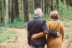 Mature couple walking in autumn park Stock Images