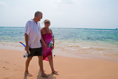 Mature couple walking on beach. Mature couple walking on tropical beach holding hands, the ocean is turquoise blue Stock Photo