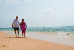 Mature couple walking on beach. Mature couple walking on tropical beach holding hands, the ocean is turquoise blue Stock Images
