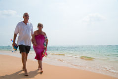 Mature couple walking on beach. Mature couple walking on tropical beach holding hands, the ocean is turquoise blue Royalty Free Stock Photography